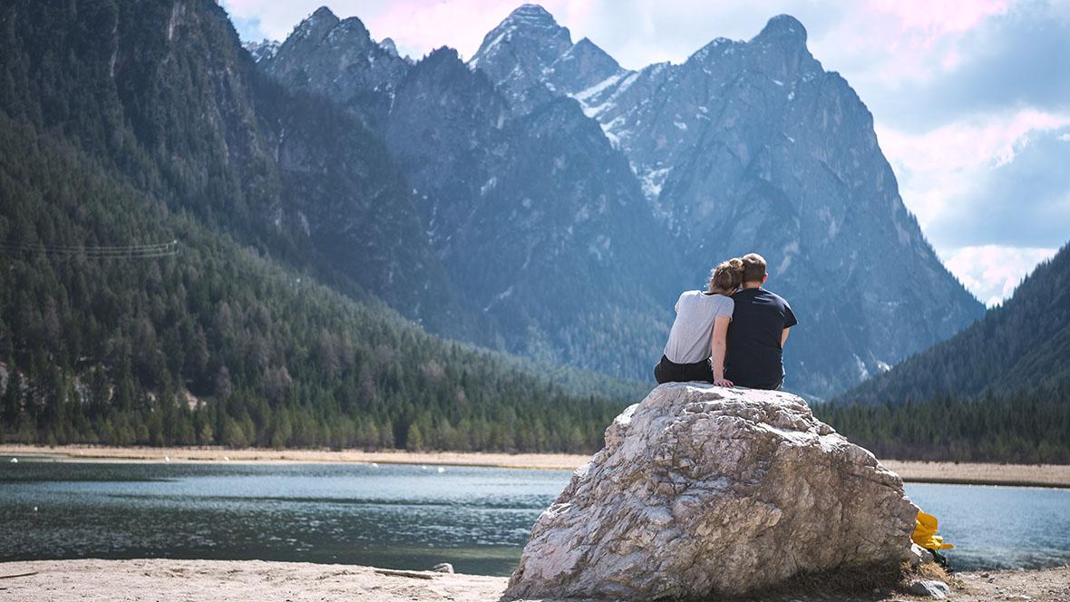 Ein Paar sitzt auf einem Fels in der Nähe eines Sees