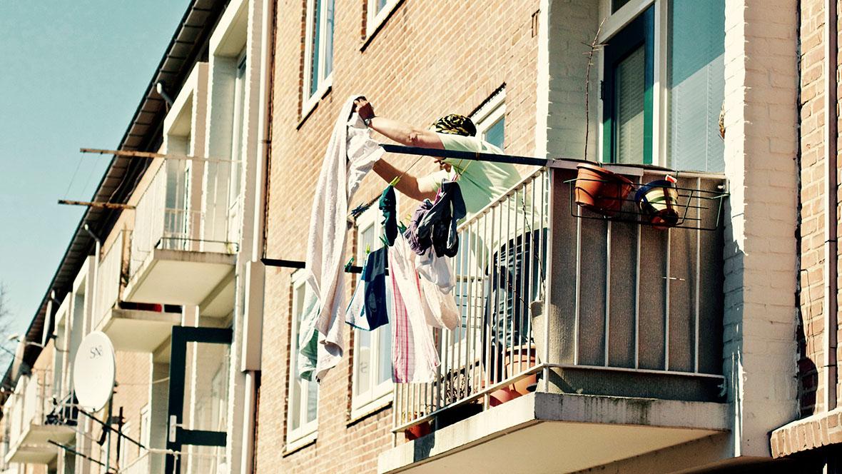 Frau hängt auf dem Balkon Wäsche auf