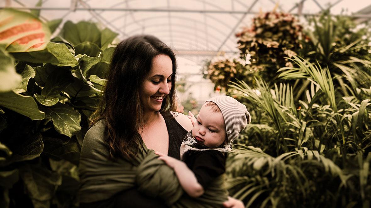 Mutter steht mit ihrem Baby auf dem Arm in einem Gewächshaus