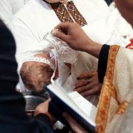 Taufpaten begleiten den Täufling bei der Taufe