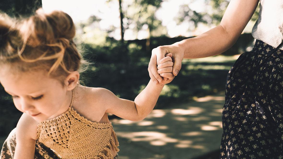 Mädchen läuft mit seiner Mutter an der Hand durch einen Park