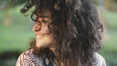 Ein Frau mit Lockenkopf lächelt glücklich. Dennoch wird die Vorfreude auf ein Baby während der Frühschwangerschaft durch einige Sorgen oft ein wenig gedämpft.