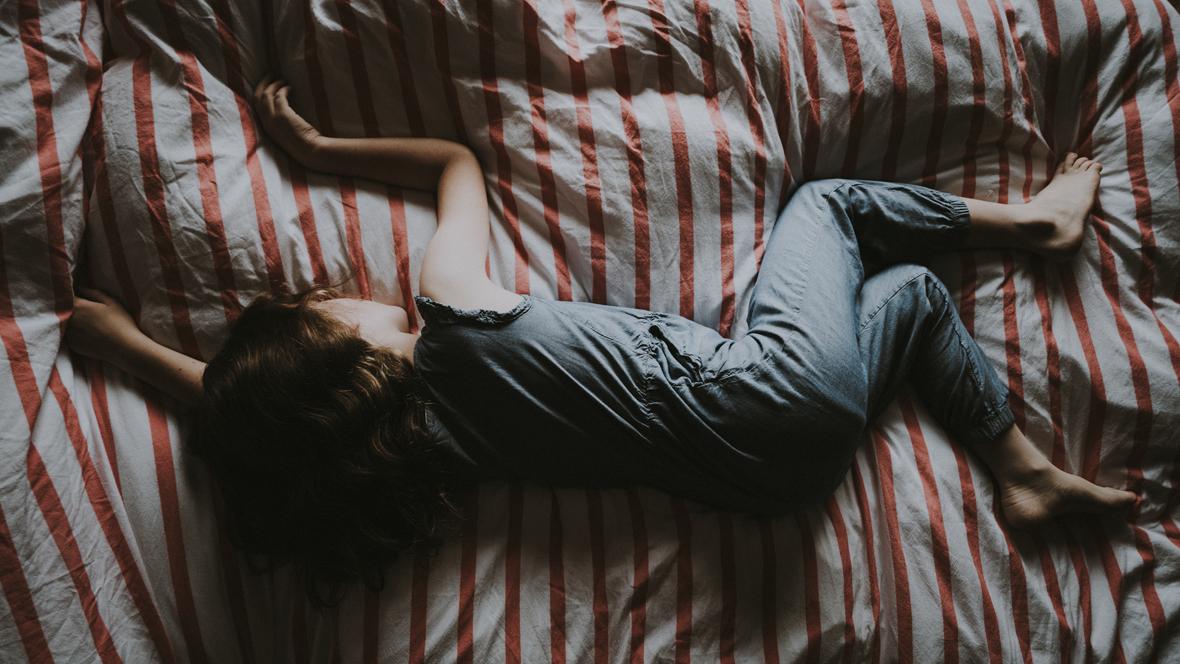 Kind liegt mit Wachstumsschmerzen im Bett
