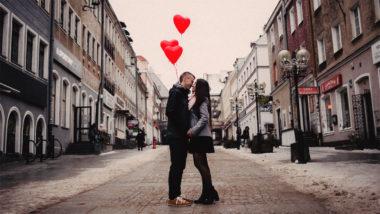 Frau und Mann küssen sich und halten Herzluftballons in der Hand