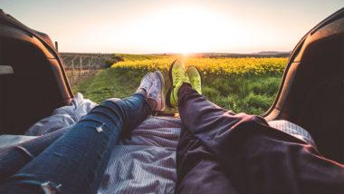 Paar liegt im Kofferraum und schaut auf ein Feld