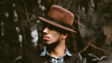 Ein Mann mit Hut steht vor Bäumen