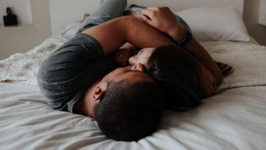 Paar liegt kuschelnd im Bett und will schnell schwanger werden