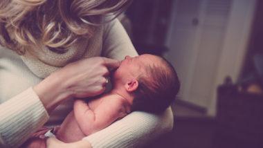 Mutter trägt Neugeborenes auf dem Arm
