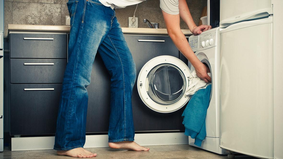 Mann steck Wäsche in die Waschmaschine