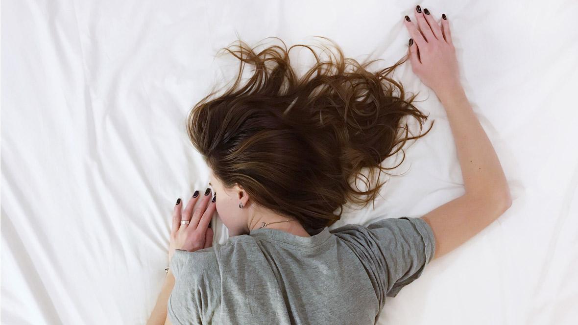 Frau liegt müde auf dem Bett