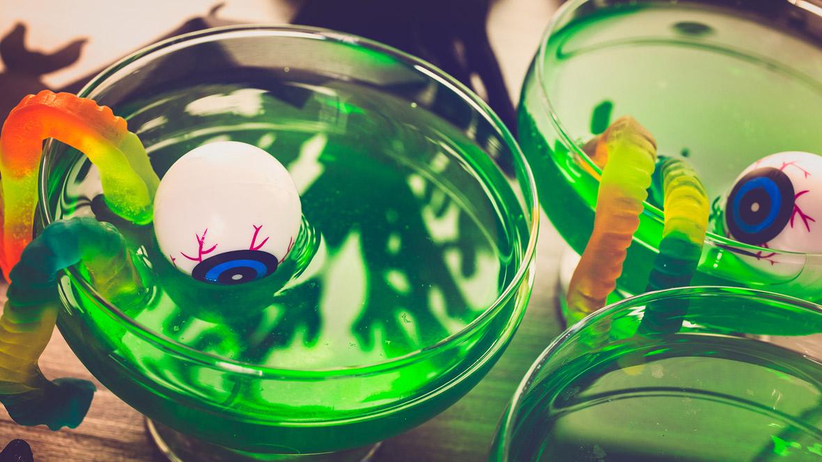 Augen und Gummi-Würmer schwimmen in einem giftgrünen Getränk - eine schaurig-schöne Halloween-Bowle