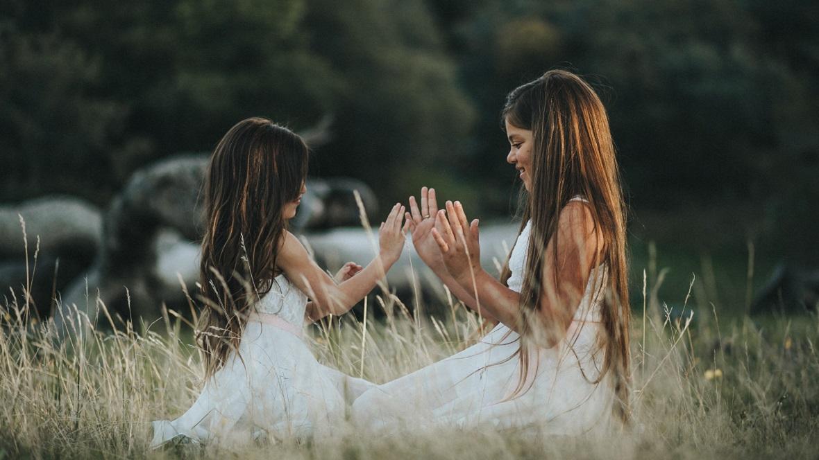 Zwei Schwestern sitzen im Gras und spielen