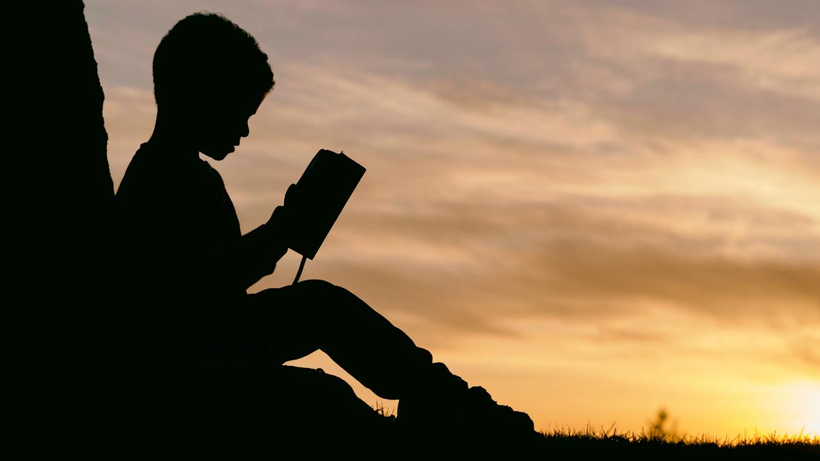 Ein Junge liest beim Sonnenuntergang