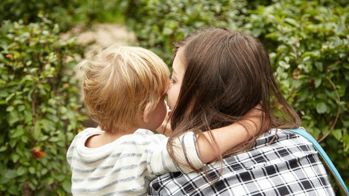 Eine Mutter flüstert ihrem Sohn etwas ins Ohr.