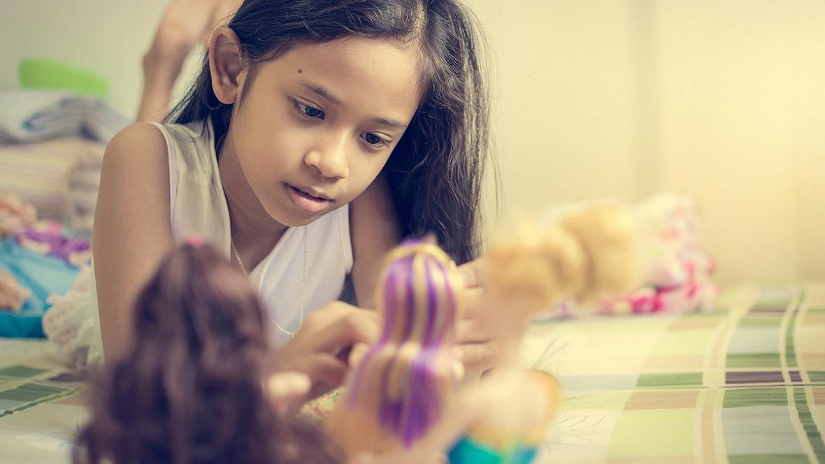 Mädchen spielt mit Barbies
