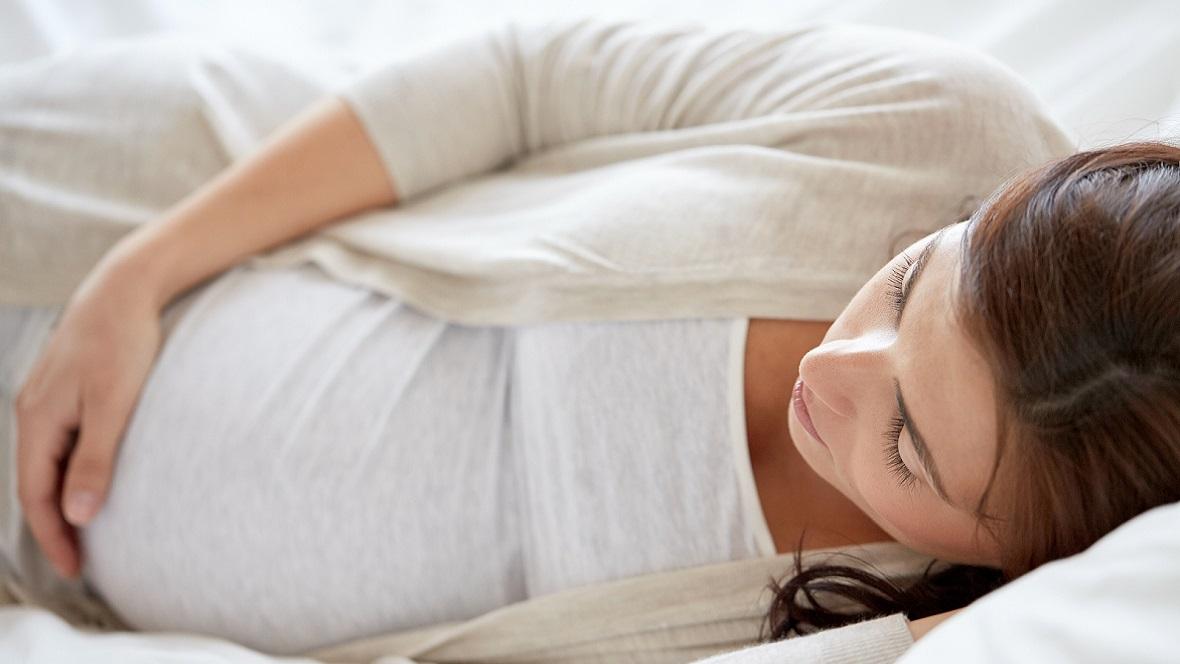 Schwangere schläft auf der linken Körperseite