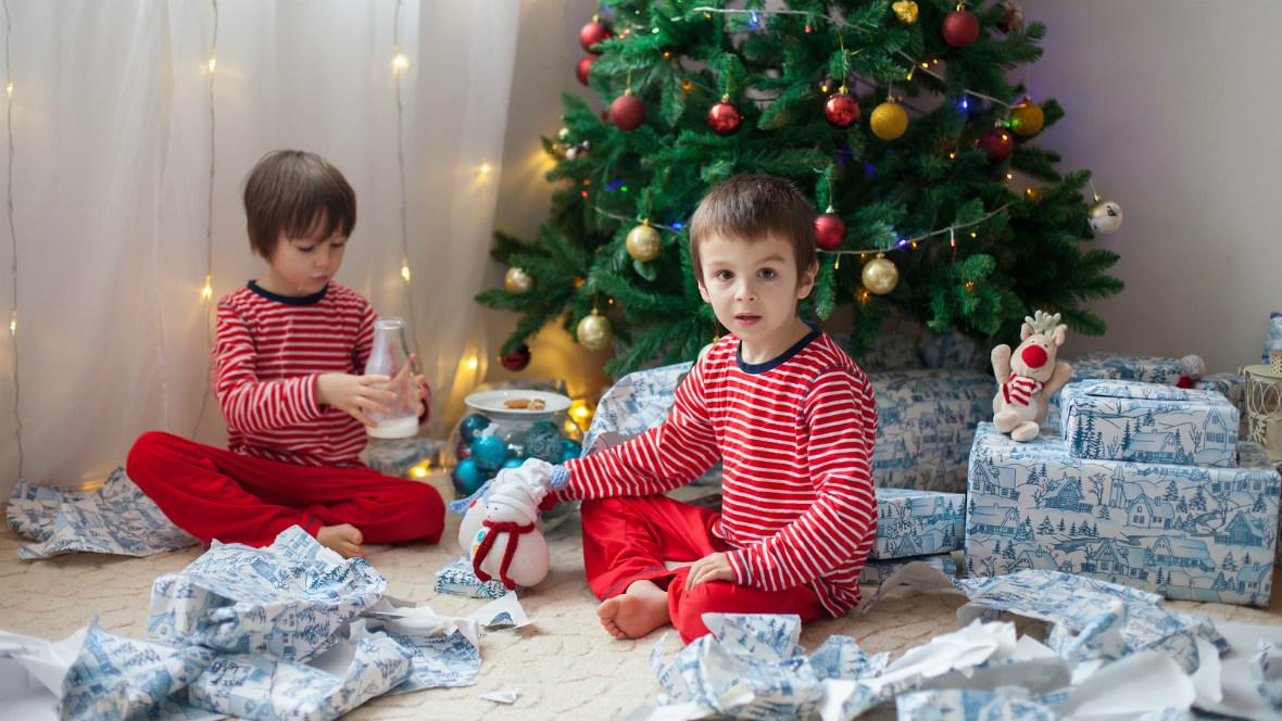 Zwei Kinder sitzen mit ihren Geschenken unter dem Weihnachtsbaum.