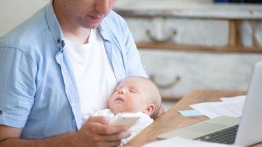 Vater schaut auf sein Handy während er sein Baby hält
