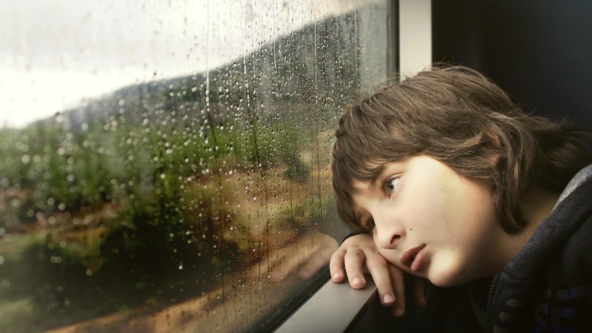 Ein Junge starrt aus dem Zugfenster