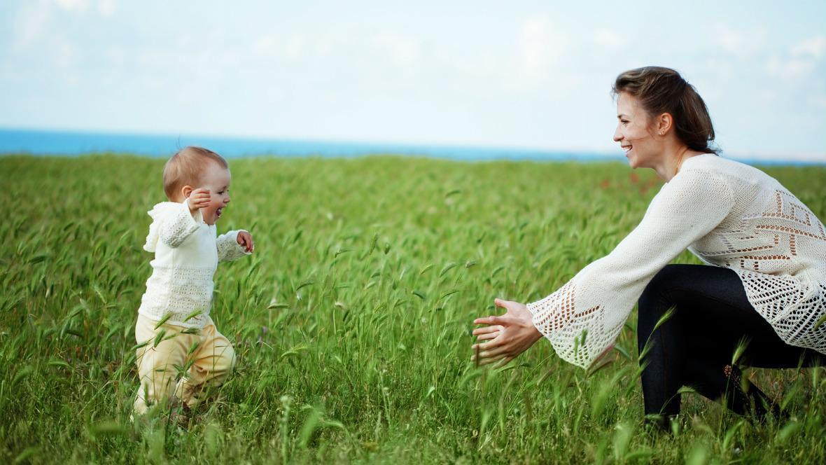Ein kleiens Kind rennt seiner Mutter auf einem Feld entgegen
