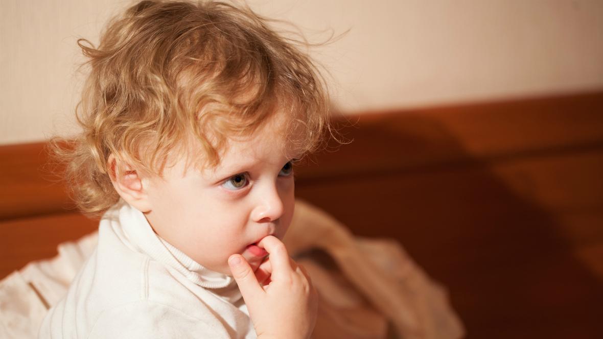Ein kleiner Junge kaut an seinem Finger