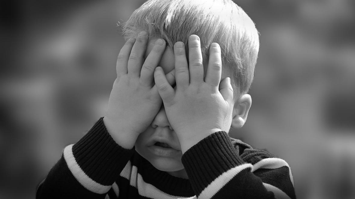 Ein kleiner Junge versteckt sein Gesicht hinter den Händen