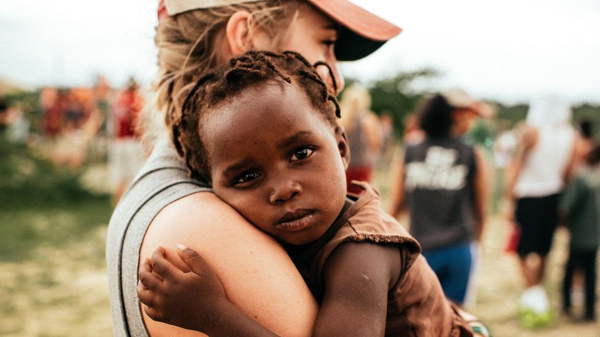Frau umarmt afrikanisches Kind