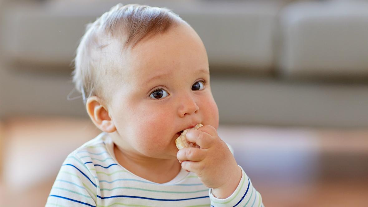 Ein kleines Kind isst eine Reiswaffel