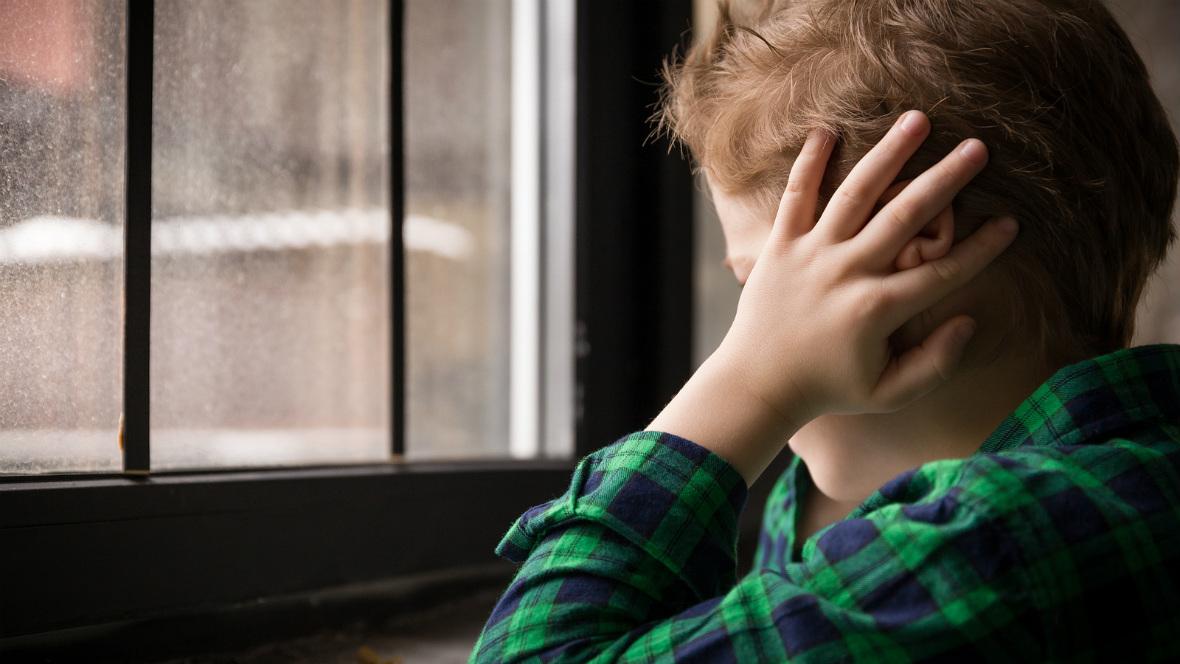 Ein Junge sitzt am Fenster und hält sich die Ohren zu