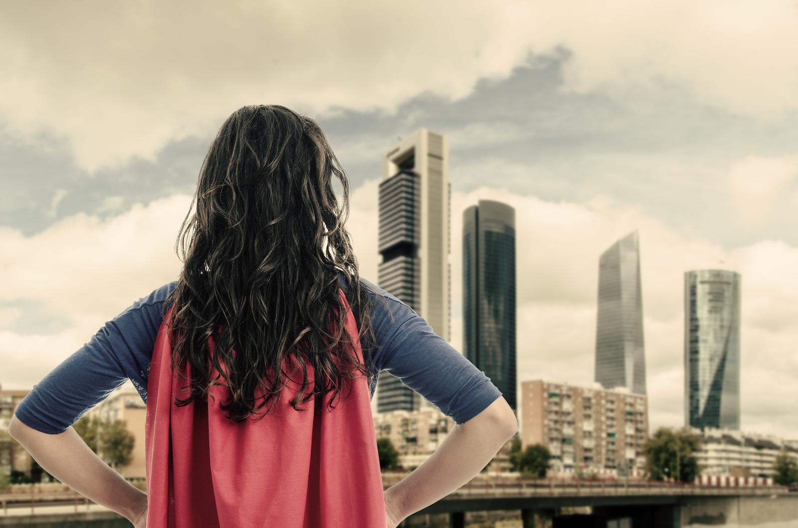 Frau mit Superheldenkostüm schaut auf eine Stadt