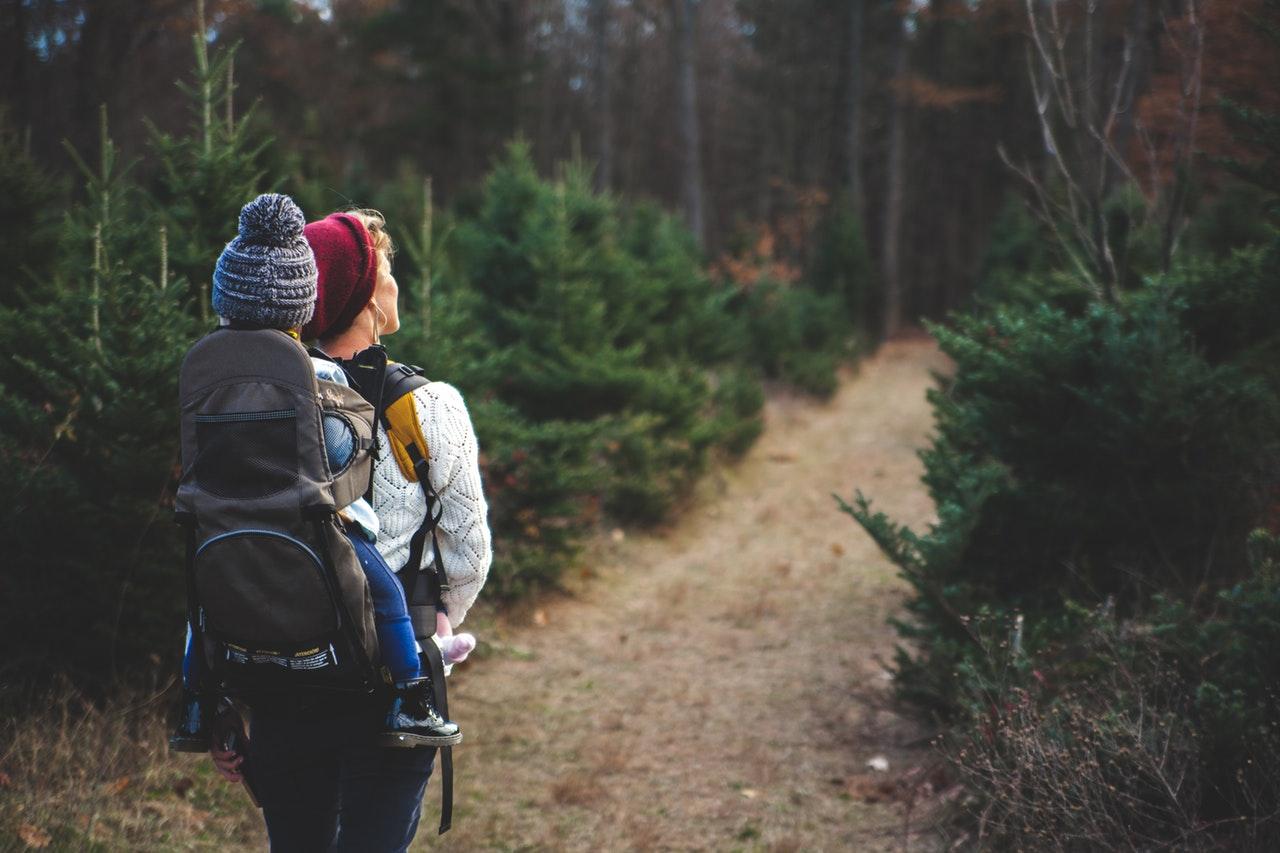 Mutter geht mit Kind auf dem Rücken im Wald spazieren