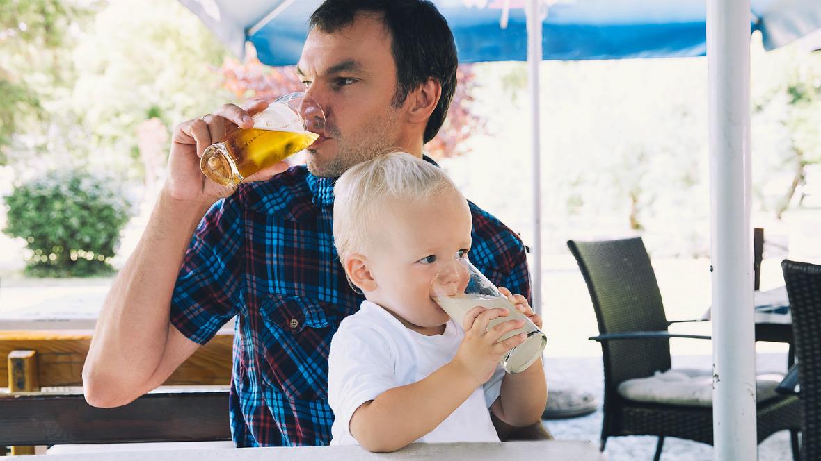 Vater und Sohn sitzen zusammen am Tisch und trinken etwas.