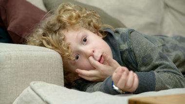 Ein Junge liegt auf der Couch und popelt