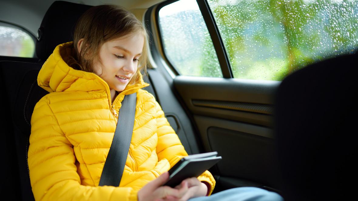 Ein Kind sitzt im Auto und liest