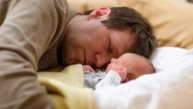 Vater schläft mit Baby auf einem Bett