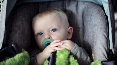 Ein kleiner Junge sitzt mit seinem Schnuller im Mund im Kindersitz