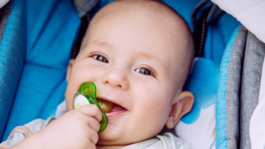 Ein glückliches Baby mit Schnuller sitzt in einem Kinderwagen