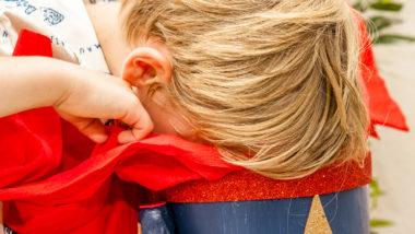Junge will Schultüte basteln und schaut in eine Tüte
