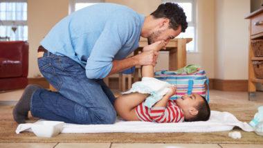 VAter wechselt seinem Baby die Windeln