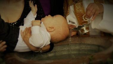 Ein Kind empfängt die Taufe über dem Taufbecken