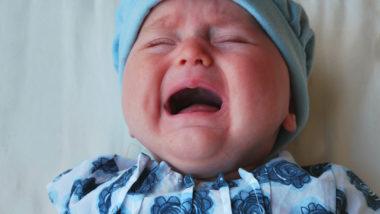 Schreinendes Baby liegt in bett