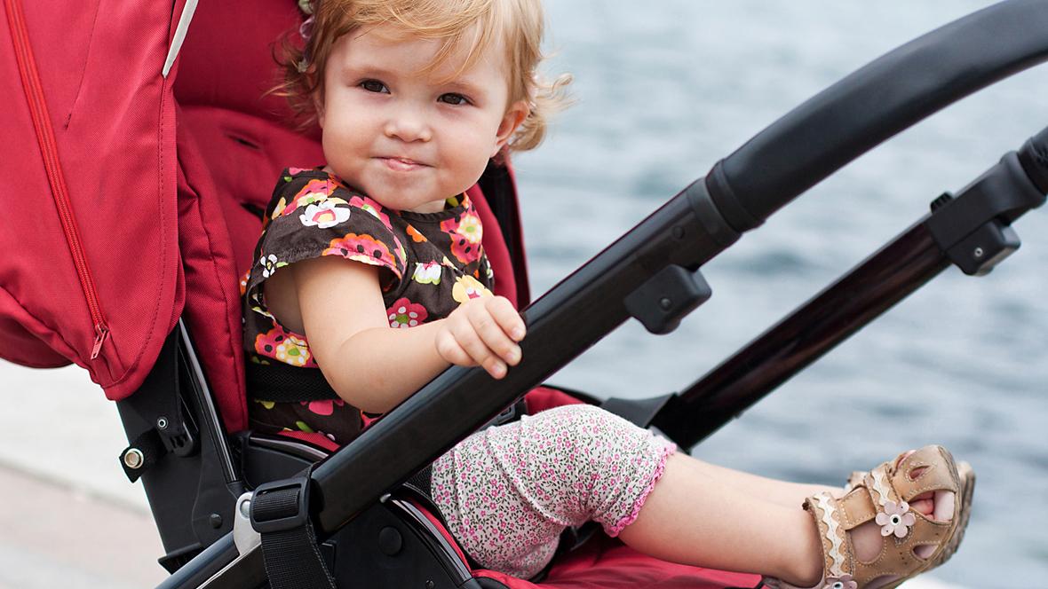 kleines Mädchen sitzt in Buggy