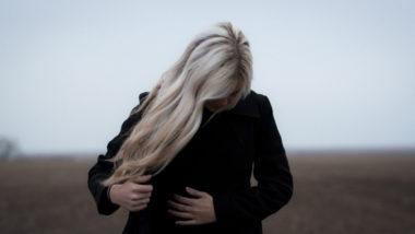 Traurige Frau mit schwarzem Mantel