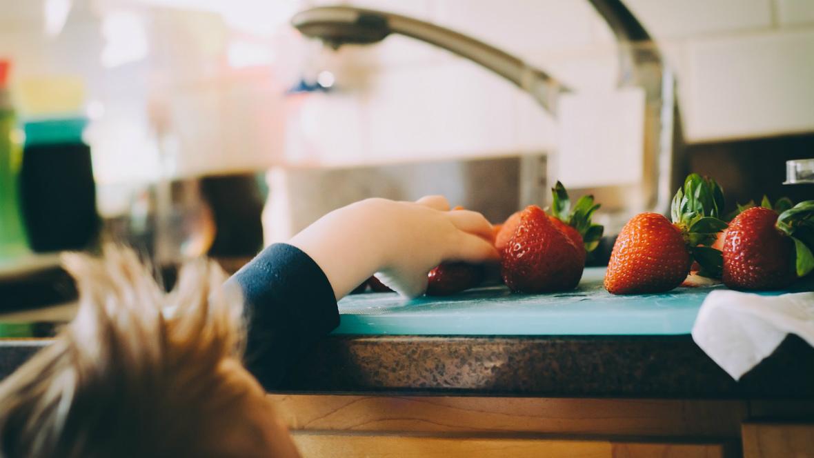 Ein Kind greift nach Erdbeeren