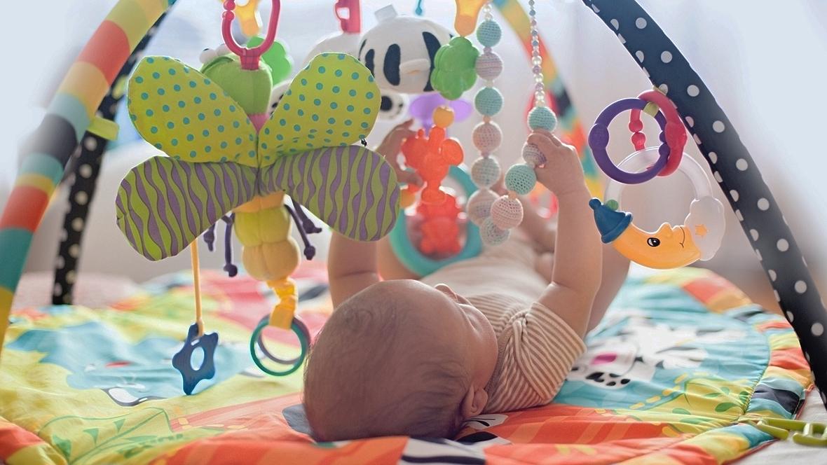 Baby liegt unter Spielbogen