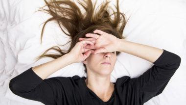 Junge Frau liegt verzweifelt auf dem Bett