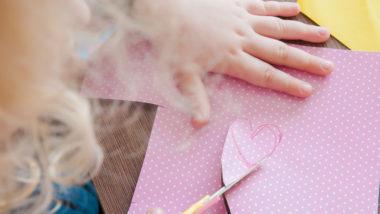 Kind schneidet herz aus rosa papier aus