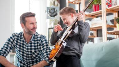 Papa hört Sohn beim Gitarrespielen