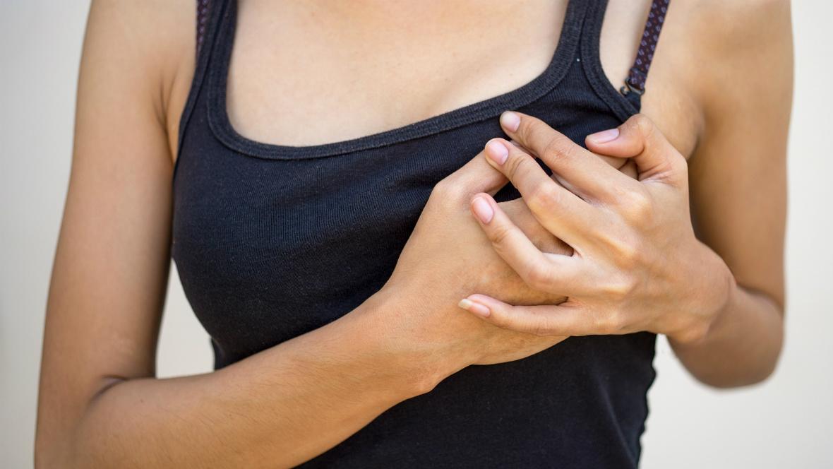 Eine Frau hält sich ihre Brust