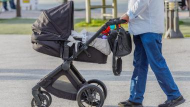 Vater geht mit Kinderwagen spazieren